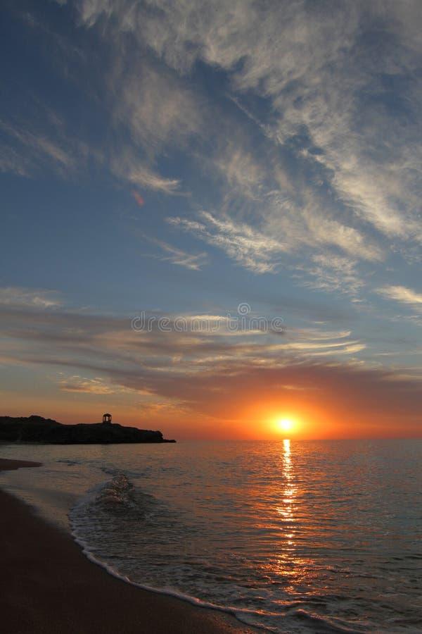 Por do sol no mar, no Sandy Beach e nas rochas na distância foto de stock