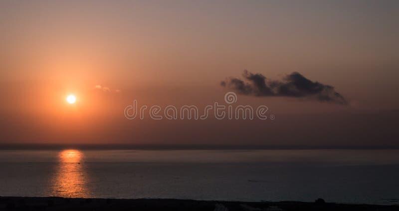Por do sol no mar Sol brilhante no céu Praia vulcânica de Havaí fotografia de stock royalty free