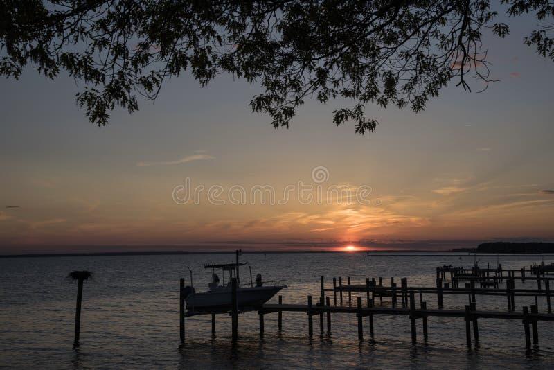Por do sol no rio que mostra as docas imagens de stock