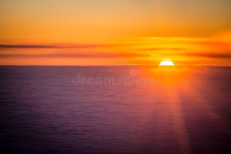 Por do sol ou nascer do sol de um avião que espreita através das nuvens imagem de stock royalty free