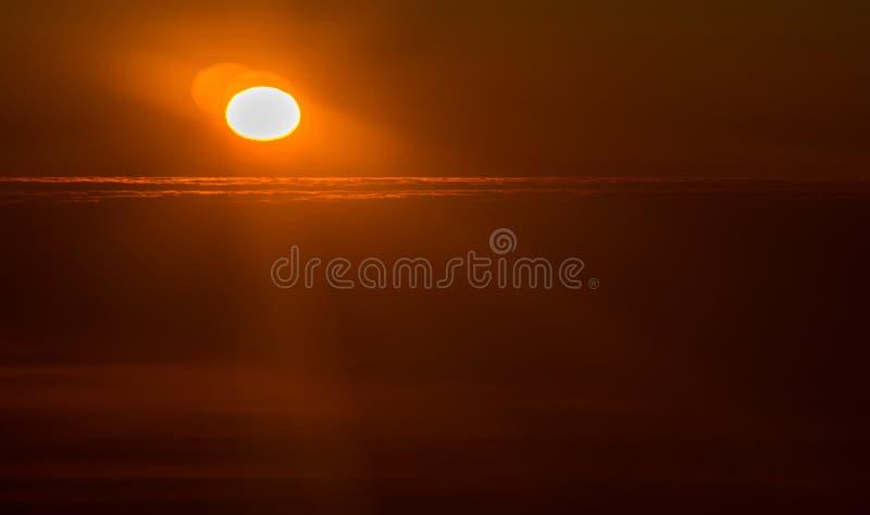 Por do sol ou nascer do sol de um avião que espreita através das nuvens foto de stock royalty free