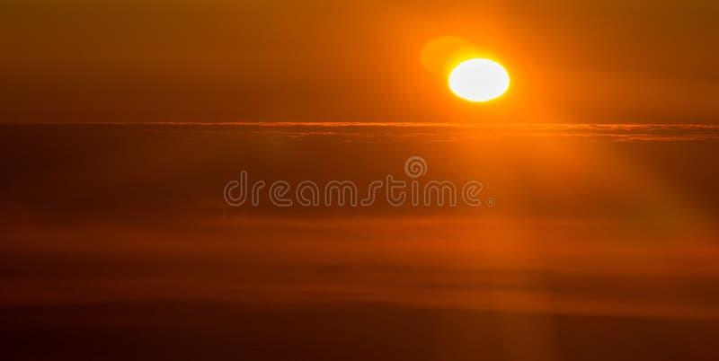 Por do sol ou nascer do sol de um avião que espreita através das nuvens fotografia de stock royalty free