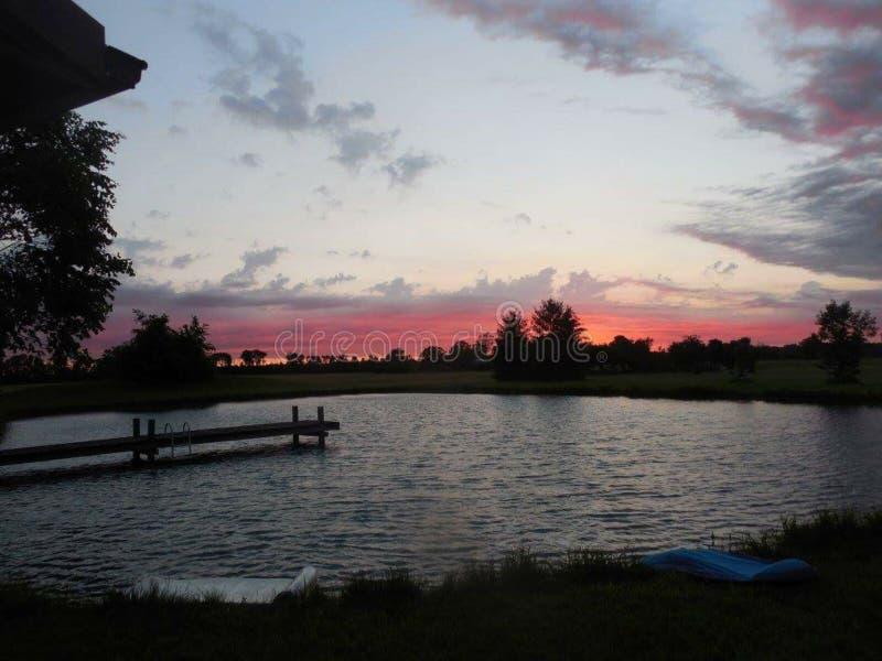 Por do sol do país pela lagoa fotos de stock royalty free