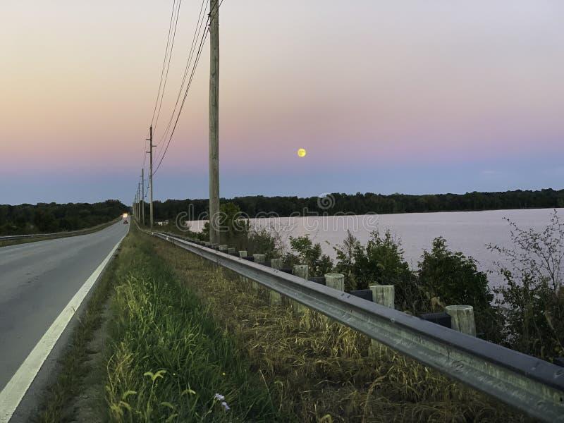 Por do sol pela estrada do lago fotografia de stock royalty free