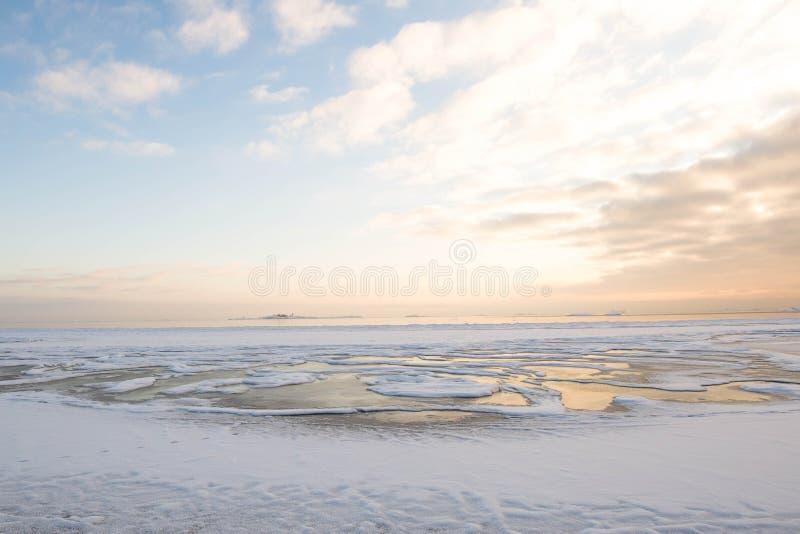Por do sol pela praia, mar gelado do inverno fotos de stock