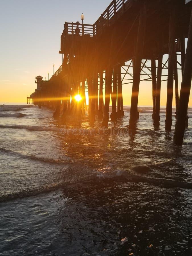 Por do sol do perto do oceano no cais fotos de stock