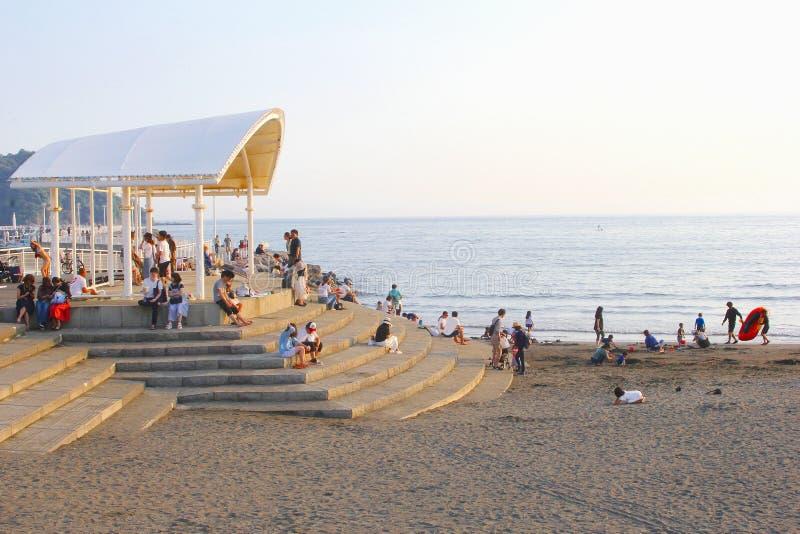 Por do sol do relógio da construção da areia da praia das escadas dos povos, Enoshima, Japão foto de stock