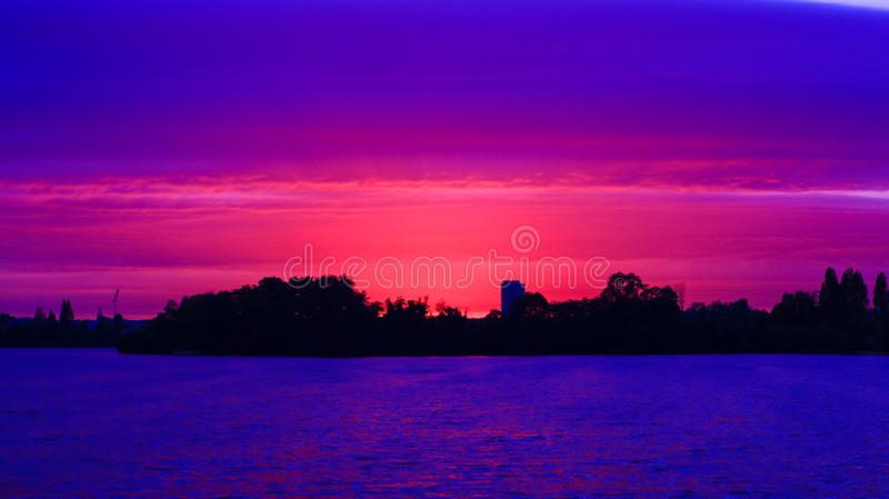 Por do sol romântico bonito atrás da silhueta de uma floresta na distância no campo fotografia de stock