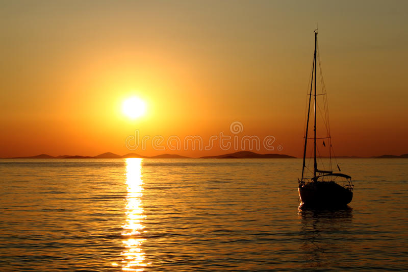 Por do sol romântico do ouro com iate fotografia de stock royalty free