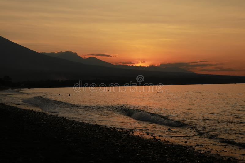 Por do sol romântico na costa de mar em Indonésia O surfista vai apreciar o paddleboard no por do sol Panorama do litoral com vul foto de stock