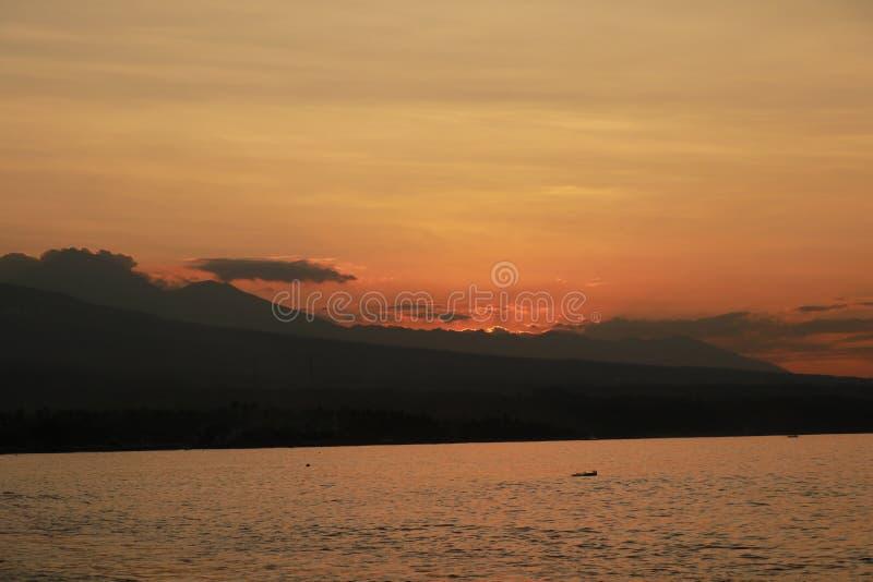 Por do sol romântico na costa de mar em Indonésia O surfista vai apreciar o paddleboard no por do sol Panorama do litoral com vul imagens de stock royalty free