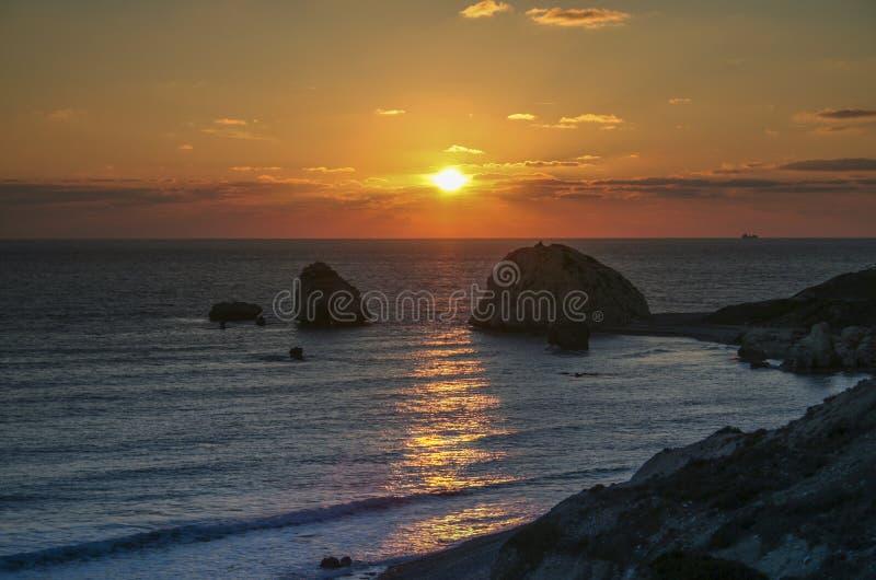 Por do sol romântico sobre uma praia rochosa em Chipre imagens de stock
