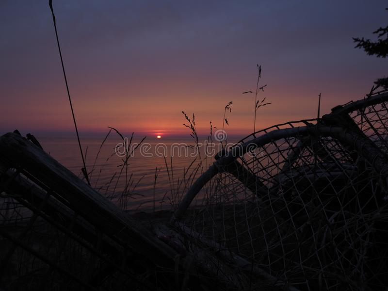 Por do sol do rosa, o roxo e o azul com as silhuetas da armadilha da lagosta no primeiro plano foto de stock royalty free
