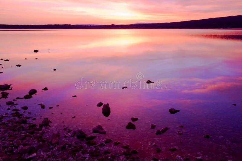 Por do sol roxo sobre a água de mar imagens de stock