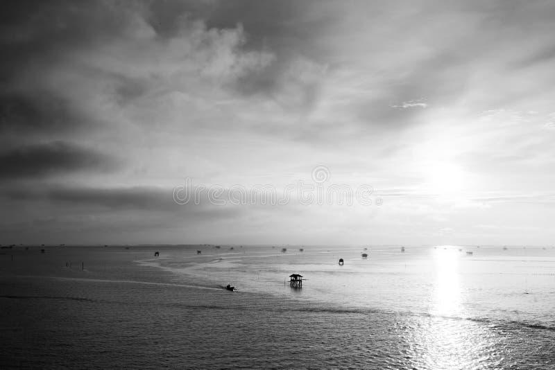 Por do sol sobre a água com céu nebuloso imagens de stock royalty free