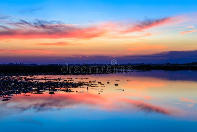 Por do sol sobre a água do lago com o céu azul dramático imagens de stock