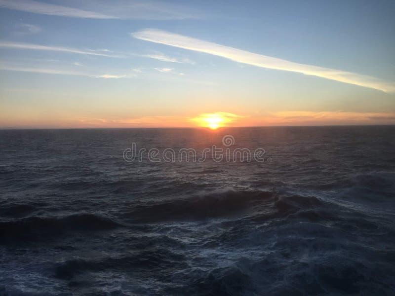 Por do sol sobre as montanhas que quebram através da nebulosidade pesada no Oceano Pacífico no Estados Unidos da América de Alask imagens de stock royalty free