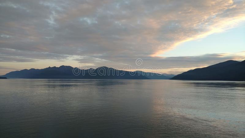 Por do sol sobre as montanhas que quebram através da nebulosidade pesada no Oceano Pacífico no Estados Unidos da América de Alask imagem de stock royalty free