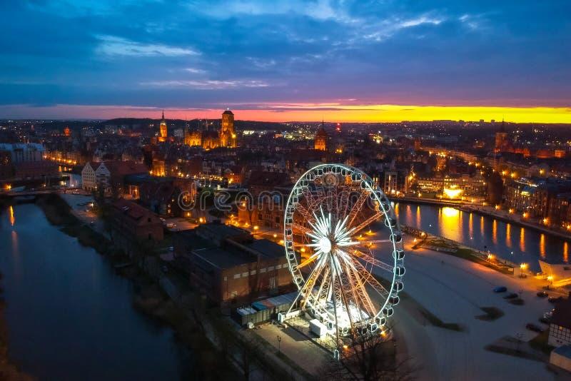 Por do sol sobre a cidade de Gdansk com a roda de ferris iluminada, Polônia imagens de stock royalty free