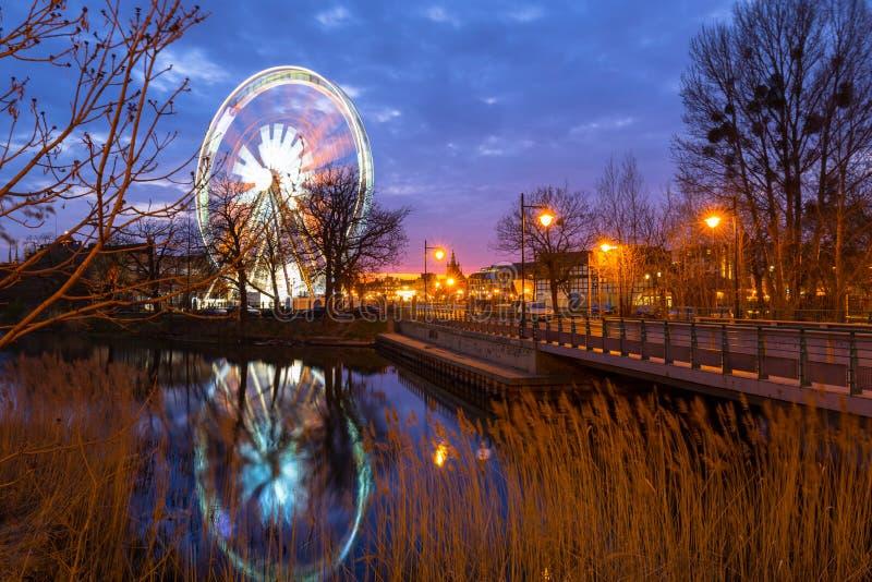 Por do sol sobre a cidade de Gdansk com a roda de ferris iluminada, Polônia imagem de stock