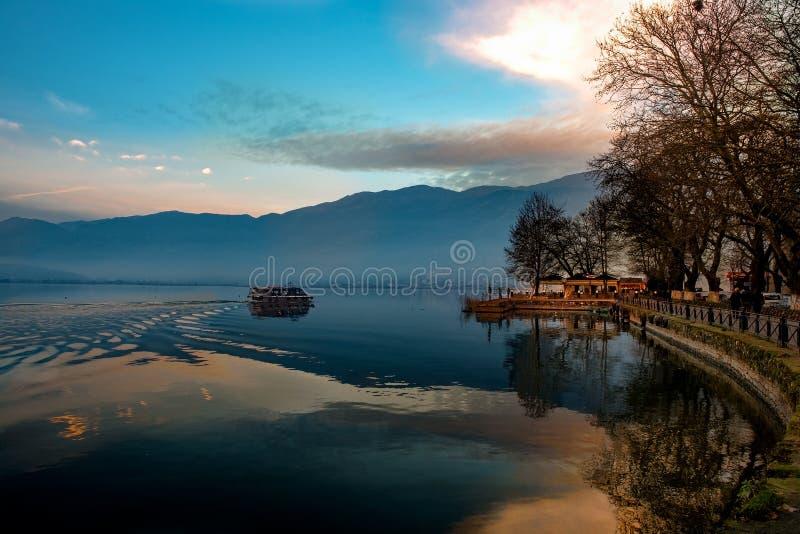 Por do sol sobre a cidade de Ioannina e o lago Pamvotis rua da frente marítima para foto de stock royalty free