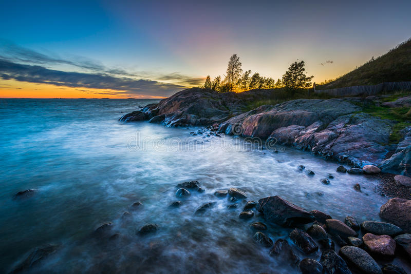 Por do sol sobre a costa rochosa em Suomenlinna, em Helsínquia, Finlandia fotos de stock royalty free
