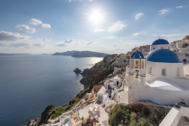 Por do sol sobre igrejas abobadadas azuis no Caldera em Oia na ilha grega de Santorini imagem de stock