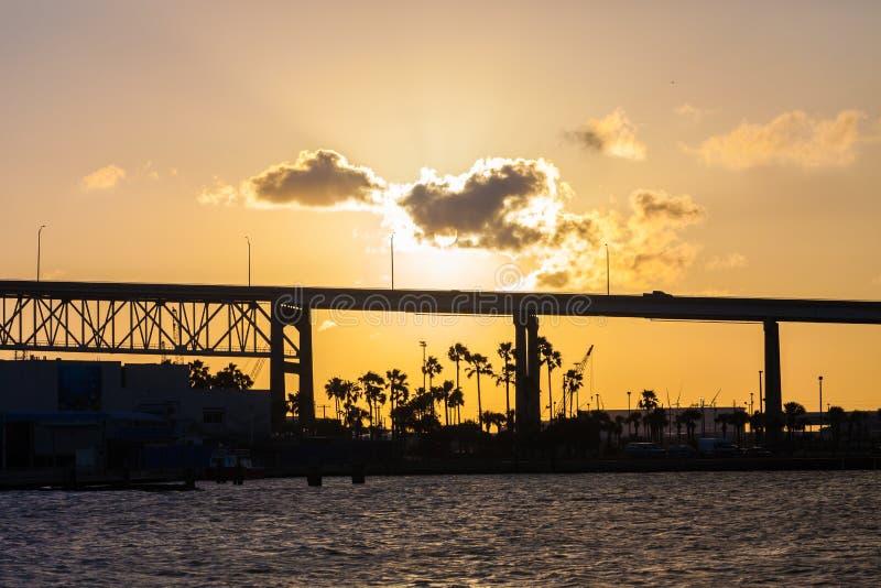 Por do sol sobre a lagoa com a silhueta do cacho da ponte e da palma imagem de stock