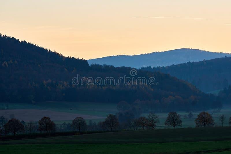 Por do sol sobre montes com forrests e campos foto de stock royalty free