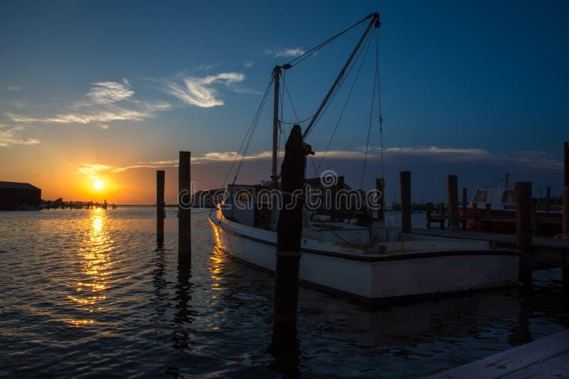 Por do sol sobre o barco de pesca de A no som de Tânger imagem de stock