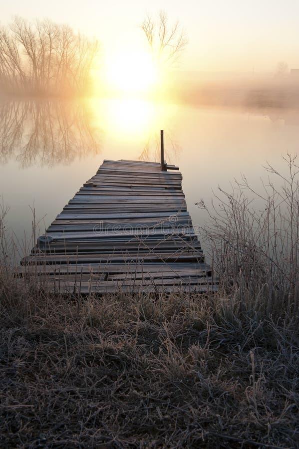 Por do sol sobre o cais no lago foto de stock