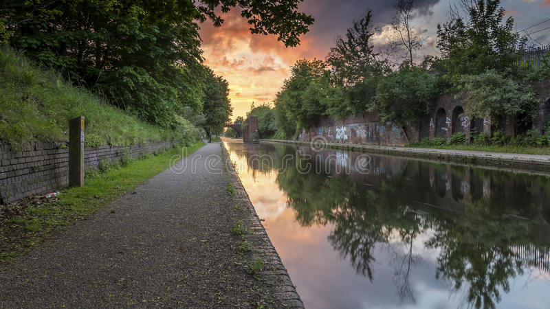 Por do sol sobre o canal em Birmingham, Reino Unido, em um passeio abandonado, com a folha que flanqueia o trajeto do reboque imagens de stock