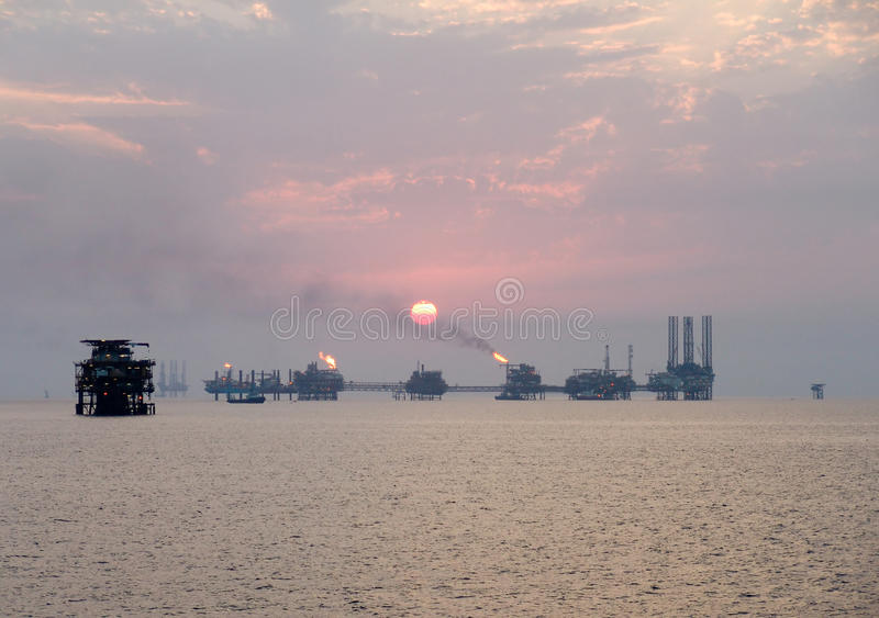 Por do sol sobre o complexo do petróleo imagens de stock