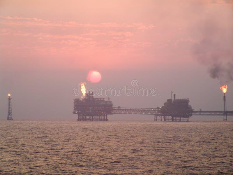 Por do sol sobre o complexo do petróleo no Golfo Pérsico fotos de stock royalty free