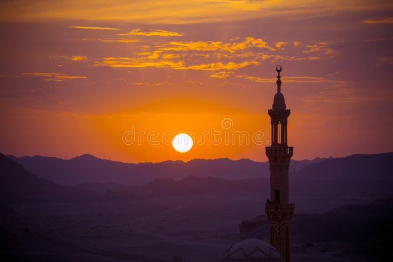 Por do sol sobre o deserto com a mesquita muçulmana no fotos de stock royalty free