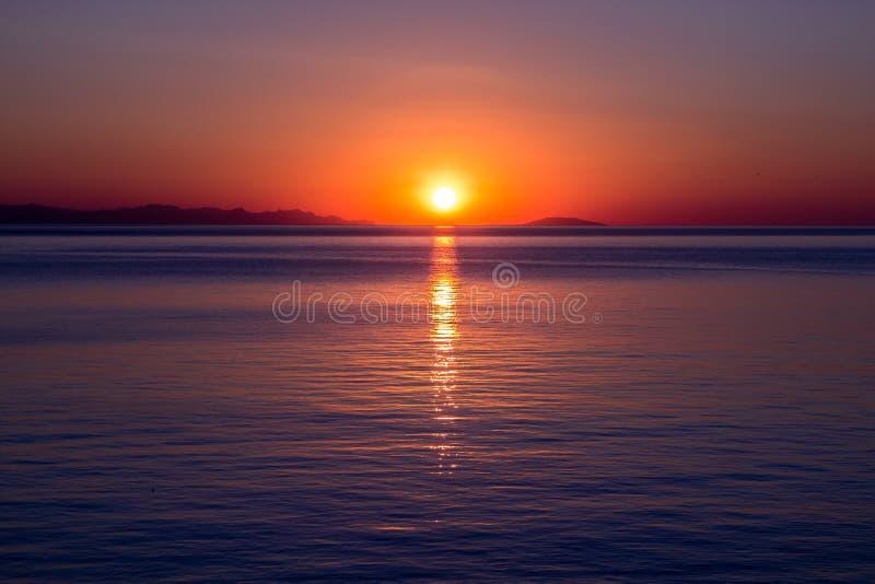 Por do sol sobre o horizonte de mar O sol brilhante é refletido da superfície da água, nivelando o céu fotos de stock royalty free