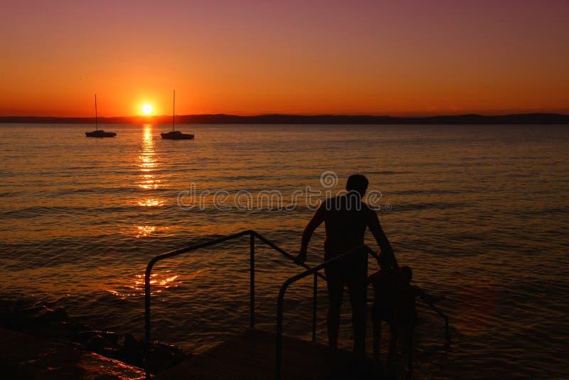 Por do sol sobre o lago com as silhuetas dos navios e dos povos fotografia de stock