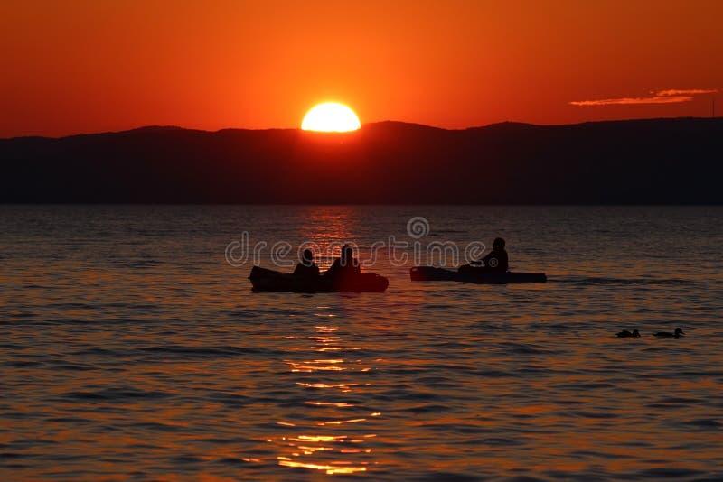 Por do sol sobre o lago com barcos e patos fotos de stock royalty free