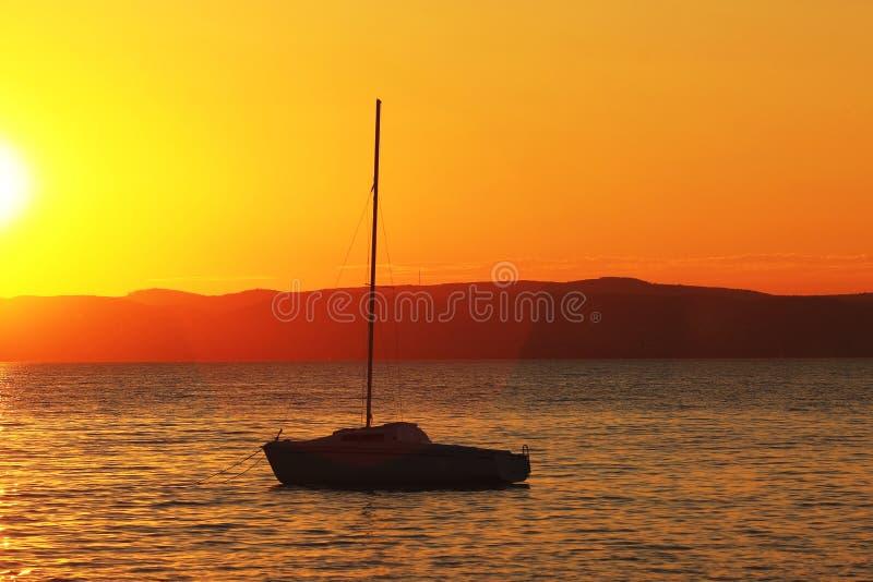 Por do sol sobre o lago com navio imagens de stock