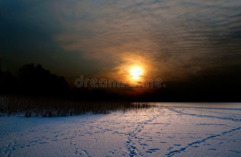 Por do sol sobre o lago no inverno imagem de stock