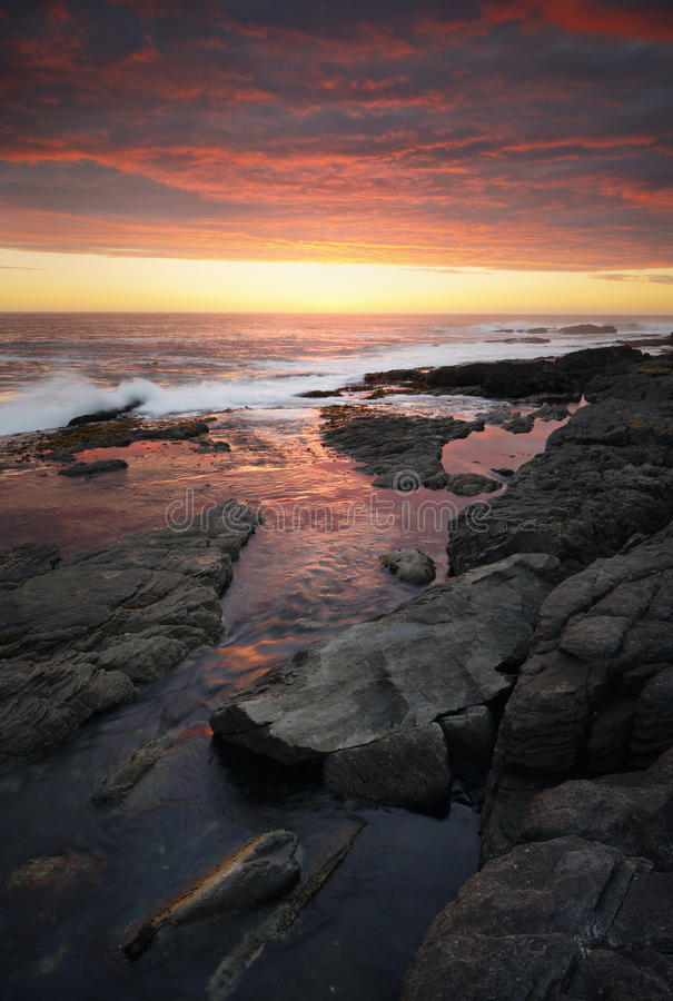 Por do sol sobre o litoral rochoso foto de stock