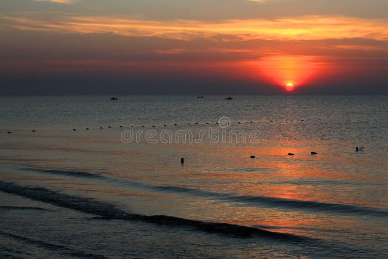 Por do sol sobre o mar com os pescadores em barcos imagem de stock royalty free