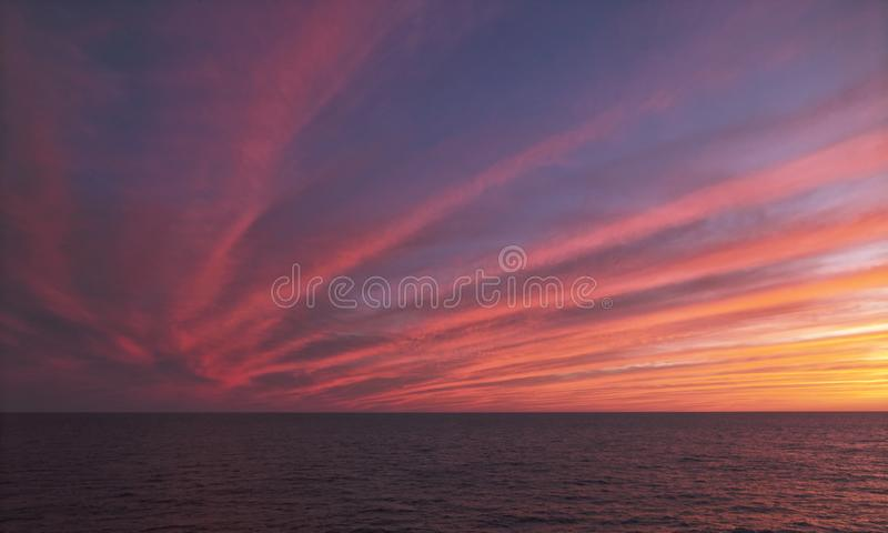 Por do sol sobre o mar, linhas da separação clara com cor cor-de-rosa saturada fotografia de stock