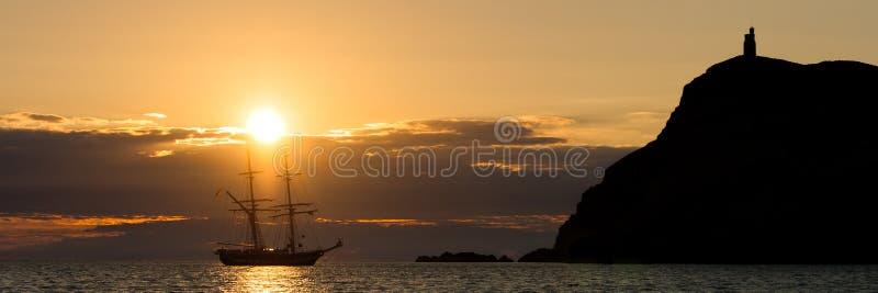 Por do sol sobre o navio alto do vintage ao lado do promontório no porto Erin na ilha do homem imagens de stock