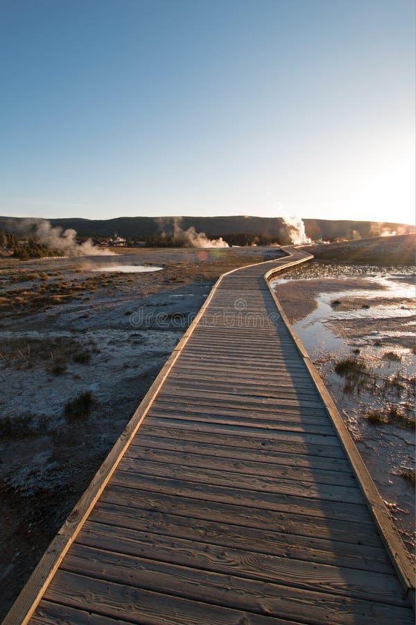 Por do sol sobre o passeio à beira mar na bacia fiel velha do geyser no parque nacional de Yellowstone em Wyoming EUA fotografia de stock