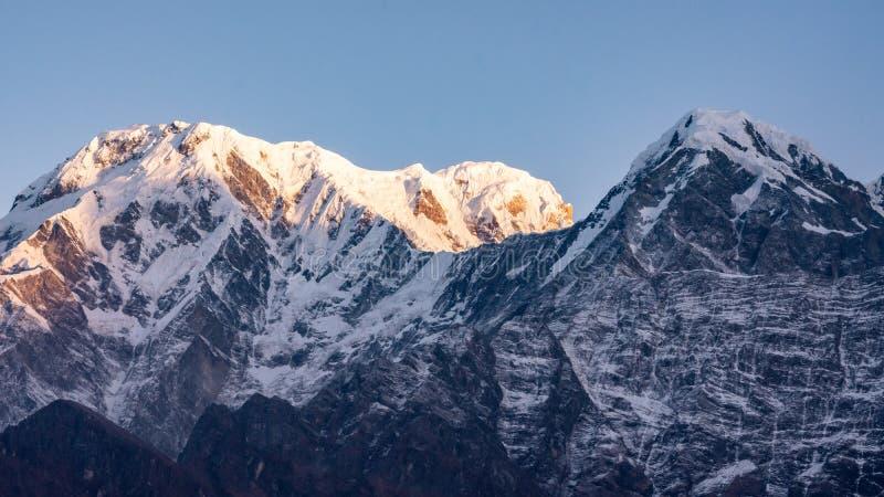 Por do sol sobre o pico de montanha snowcapped Annapurna sul em Nepal fotos de stock