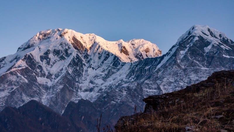Por do sol sobre o pico de montanha snowcapped Annapurna sul nos Himalayas imagem de stock