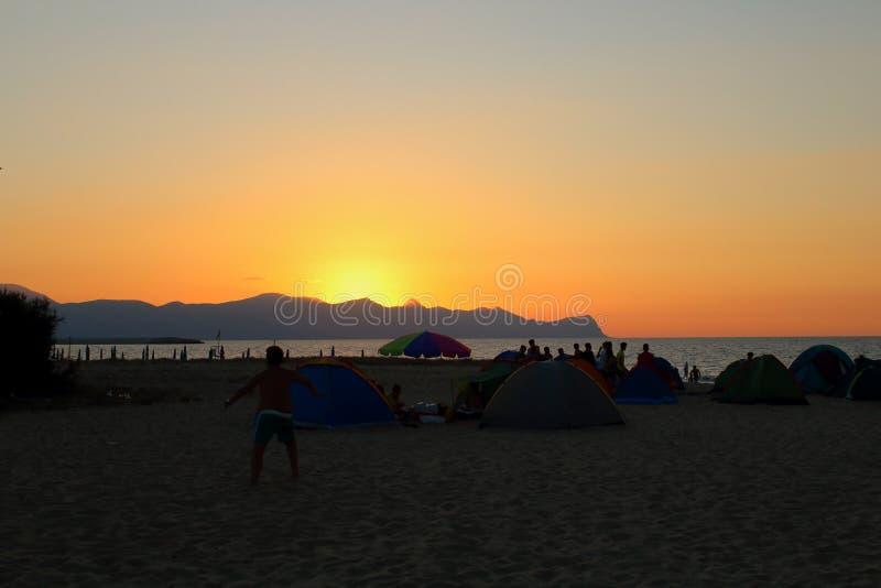 Por do sol sobre o promontório do mar no fundo e na silhueta das barracas e dos povos que acampam na praia imagem de stock