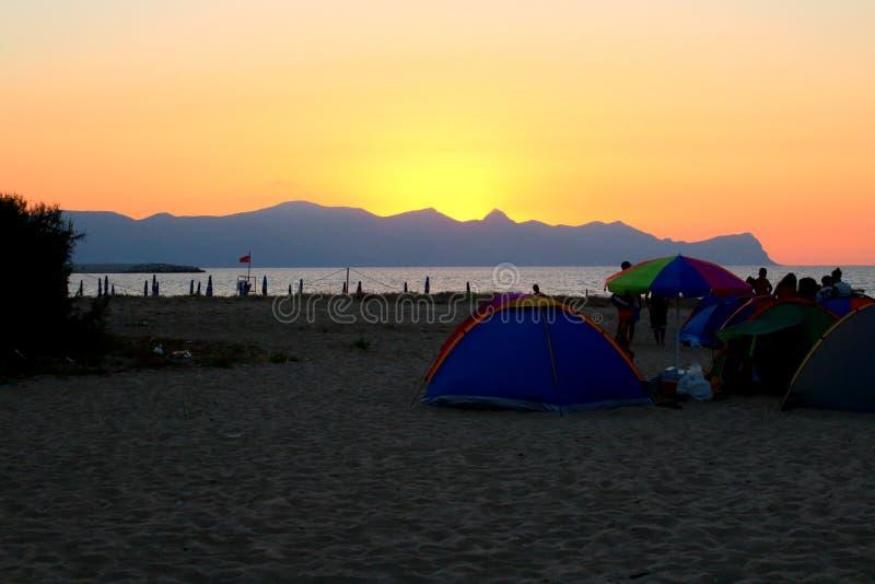 por do sol sobre o promontório do mar no fundo e na silhueta das barracas e dos povos que acampam na praia fotografia de stock
