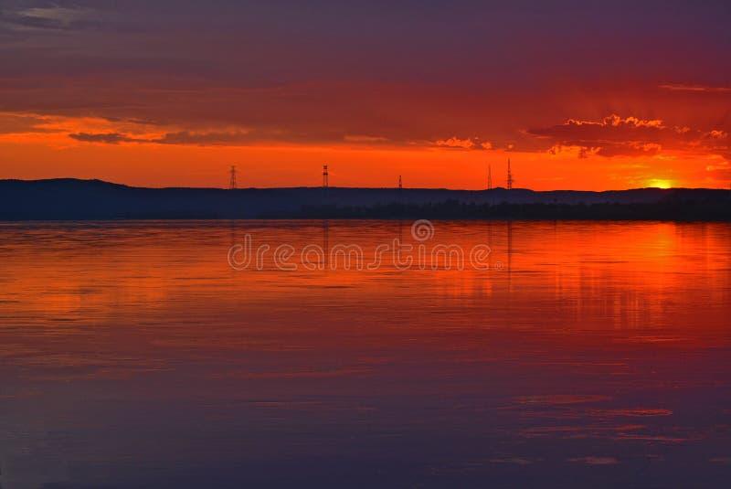 Por do sol sobre o rio A reflexão do sol de ajuste na água fotografia de stock